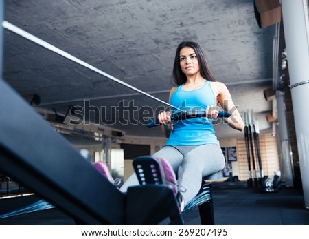 Happy charming woman working out on training simulator in fitness gym - stock photo