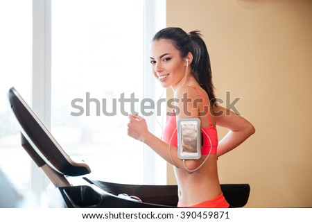 Happy charming young sportswoman running on treadmill in gym and listening to music from mobile phone  - stock photo