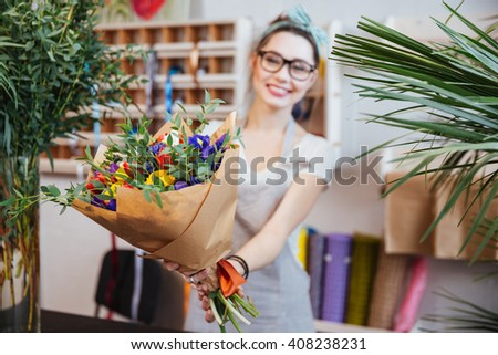 Happy charming young woman florist giving bouquet of colorful flowers to you - stock photo