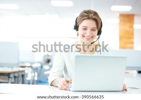 Happy charming young woman sitting and working with laptop using headset in office - stock photo