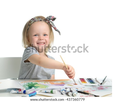 Happy cheerful baby girl child drawing with brush in album with painting tools laughing isolated on a white background - stock photo