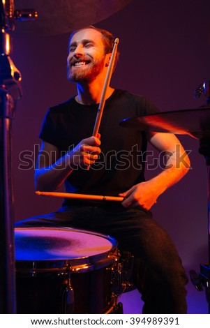 Happy cheerful bearded man drummer playing on his kit with sticks over dark background - stock photo