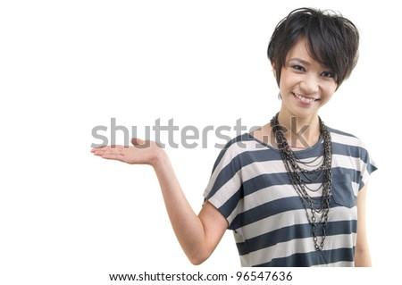 Happy cheerful beautiful Asian young woman holding her hand out and showing copy space for your product. - stock photo