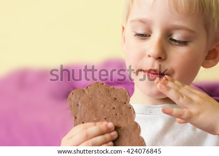 Happy cheerful boy eating a chocolate candy bar holding hands, smearing the face, soft focus - stock photo