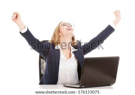 Happy, cheerful caucasain business woman sitting by the table and looking at the screen laptop. Isolated on white. - stock photo