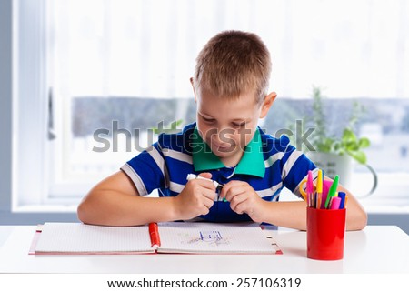 Happy cheerful child drawing with brush in album using a lot of painting tools. Creativity concept. - stock photo