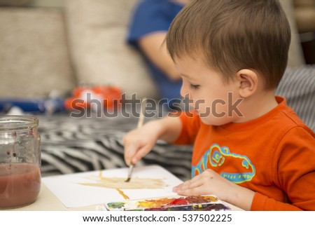 Happy cheerful child drawing with brush using a painting tools. Creativity concept