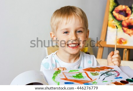 Happy cheerful child paint with   album using a lot of tools for drawing. Creativity concept boy draws paints and holds a brush, a happy childhood, soft focus - stock photo