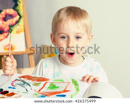 Happy cheerful child paint with brush in album using a lot of tools for drawing. Creativity concept boy draws paints and holds a brush, a happy childhood - stock photo