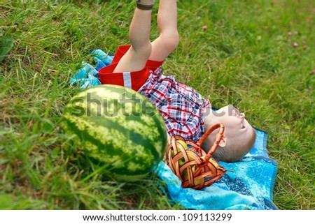 Happy cheerful child playing outdoor on the green meadow in summer day - stock photo