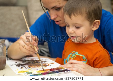 Happy cheerful child with her mother drawing with brush using a painting tools. Creativity concept