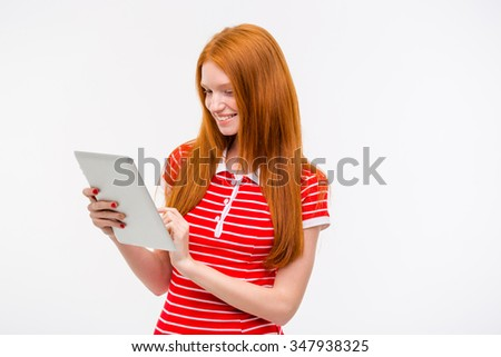 Happy cheerful content smiling redhead girl in red striped top using tablet and posing over white background - stock photo