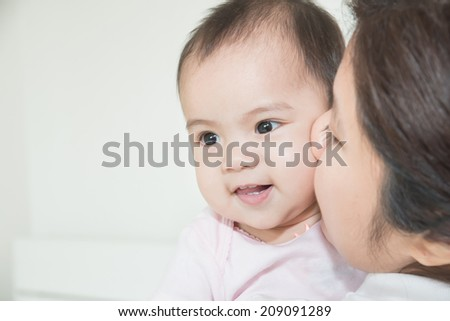 Happy cheerful family. Asian mother and baby kissing, laughing and hugging