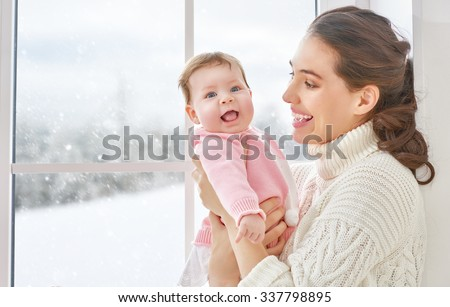Happy cheerful family. Mother and baby hugging near window. - stock photo