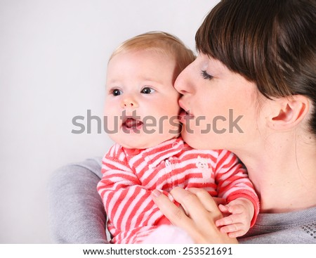 Happy cheerful family. Mother and baby kissing - stock photo