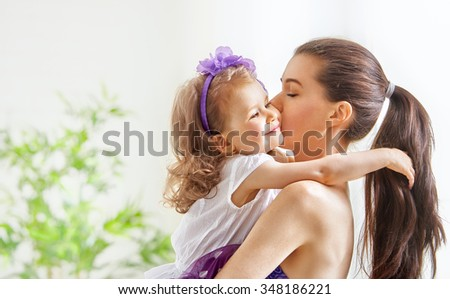 Happy cheerful family. Mother and child girl hugging  - stock photo