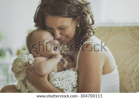 Happy cheerful family. Vintage style phot from Mother and baby, laughing and hugging. - stock photo