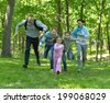 Happy cheerful family walking in summer park - stock photo