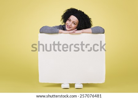 Happy cheerful girl holding a white blank paper sign board with empty copy space, isolated on yellow background. - stock photo