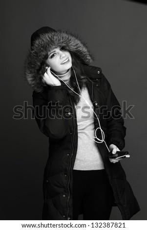 Happy cheerful girl in warm jacket with headphones - stock photo