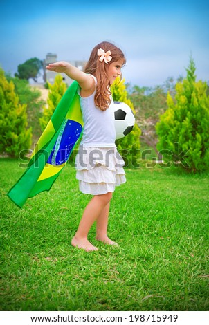 Happy cheerful girl playing with ball on backyard in sunny day, big national Brazil flag, football championship concept - stock photo