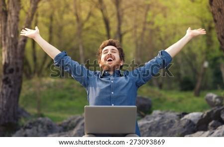 Happy cheerful hipster man with a laptop sitting outdoors in nature, freedom and happiness concept - stock photo