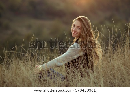 Happy,cheerful,joyful,smiling girl sitting on the hill with very incredibly,beautiful view,watch sunset.Beautiful girl sitting outdoor,in mountains,sunlight,sunny field.Attractive girl with nice smile - stock photo