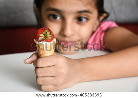 Happy, cheerful, laughing child/ kid/ young girl looking with desire/ greed at tasty sweet ice cream cone hot summer vacation/ holiday Kerala, India, Asia. Indian daughter  holding lollipop smiling. - stock photo