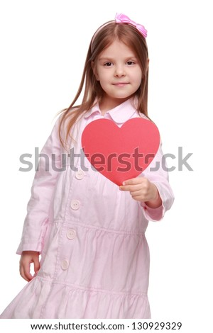 Happy cheerful little girl holding a red heart made ??of paper on Holiday