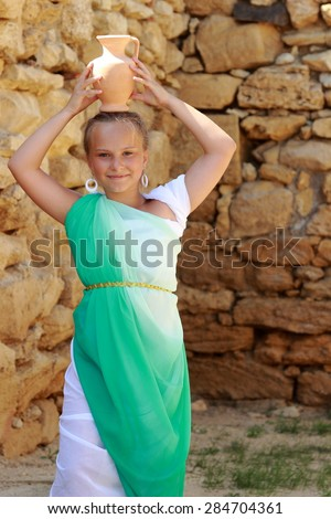 Happy cheerful little girl in a Greek tunic as a Greek goddess holding a vintage amphora on the background of the archaeological site of the ancient city of Nymphaeum in the village Geroevskoe - stock photo