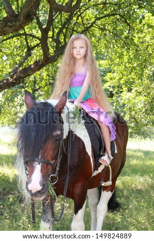Happy cheerful little girl with long healthy hair is sitting on a horse and smiling