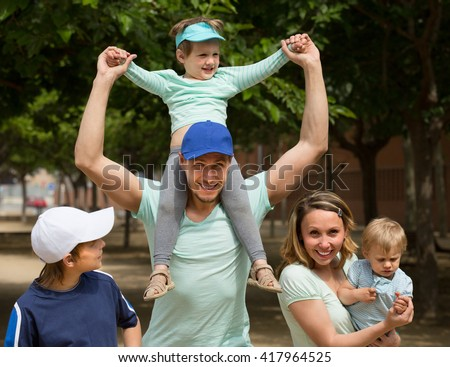 Happy cheerful parents with kids walking outdoor and smiling - stock photo