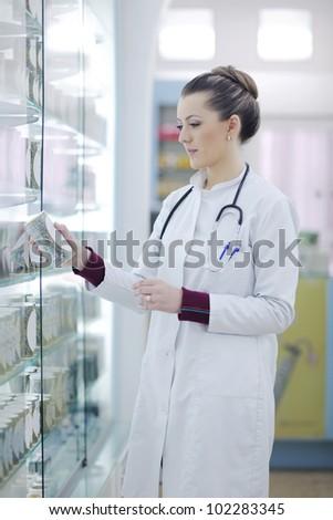 Happy cheerful pharmacist chemist woman standing in pharmacy drugstore - stock photo