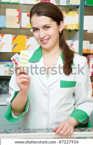 Happy cheerful pharmacist chemist woman standing in pharmacy drugstore with pills - stock photo