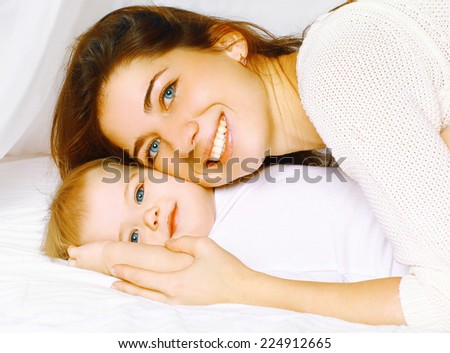 Happy cheerful portrait mother and baby in bed - stock photo