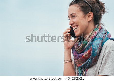 happy cheerful smiley woman by the sea talking on phone with sunglasses on summer - stock photo