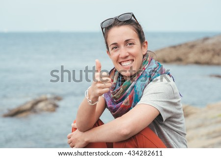 happy cheerful smiley woman sitting on a rock by the sea, giving thumbs up with sunglasses on summer - stock photo