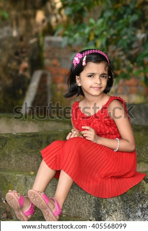 Happy cheerful smiling cute little girl/ child/ kid sitting trendy outfit naughty looks Kerala, India. Young Indian daughter enjoying day out. Girl in red frock fashion store for kids, model grooming - stock photo