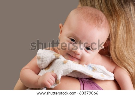 Happy cheerful ten weeks old baby girl on mother's shoulder looking at camera with smile