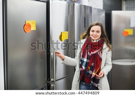 Happy cheerful woman buying domestic refrigerator in supermarket - stock photo