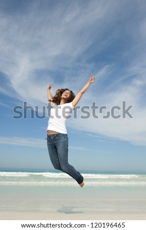 Happy cheerful young attractive woman jumping full of joy at beach with arms up, isolated with ocean and blue sky as background and copy space. - stock photo