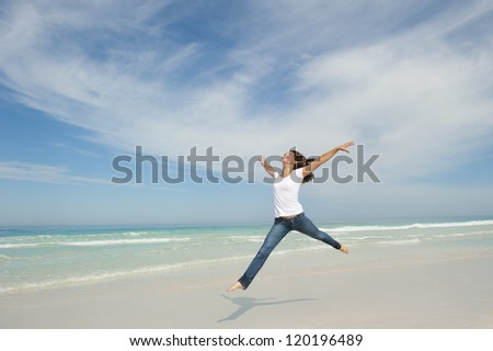 Happy cheerful young sexy woman jumping full of joy at beach with arms up, isolated with ocean and blue sky as background and copy space. - stock photo