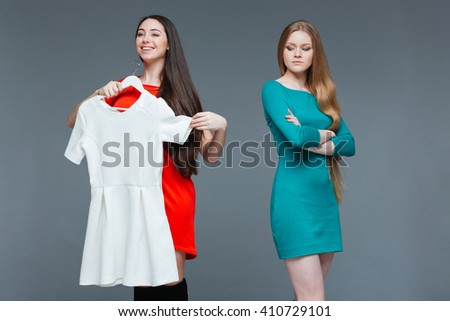 Happy cheerful young woman and envious angry female on shopping over grey background - stock photo