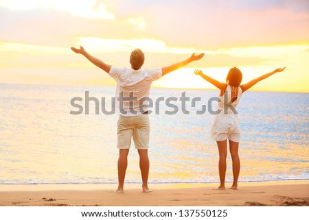 Happy cheering couple enjoying sunset at beach with arms raised up in joyful elated happiness. Happiness concept with young joyous couple, Caucasian man and Asian woman. - stock photo