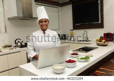 happy chef cooking in a modern kitchen smiling  and using a laptop - stock photo