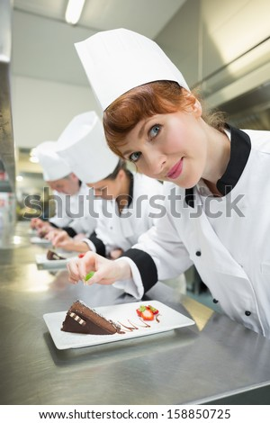 Happy chef garnishing dessert plate standing in a kitchen