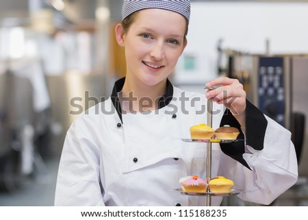 Happy chef holding tiered cake tray of cupcakes in kitchen - stock photo