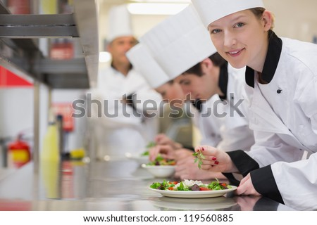 Happy chef looking up from preparing salad in culinary class - stock photo