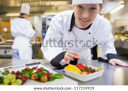 Happy chef preparing fruit salad in kitchen - stock photo