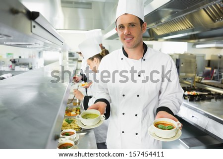 Happy chef presenting two types of soup standing in the kitchen - stock photo